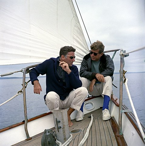 "President John F. Kennedy sails with his brother-in-law, Peter Lawford (left), aboard the United States Coast Guard yacht ""Manitou"" off the coast of Johns Island, Maine. - August 12, 1962"